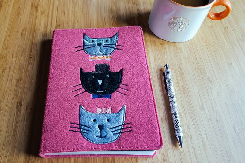 A notebook with cats on, a pen with owls on and a cup of coffee