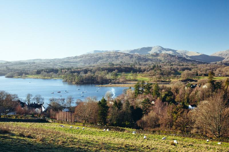 View of boats on Lake Windermere, blue sky above and fells in the background