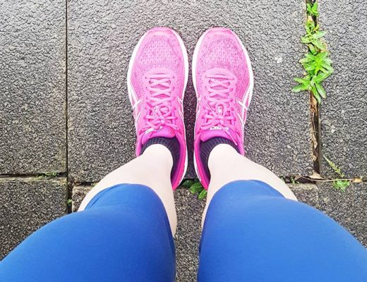 Woman's legs wearing blue running leggings and pink trainers