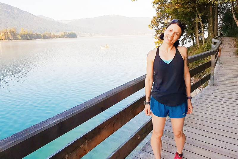 Female runner stood next to a lake