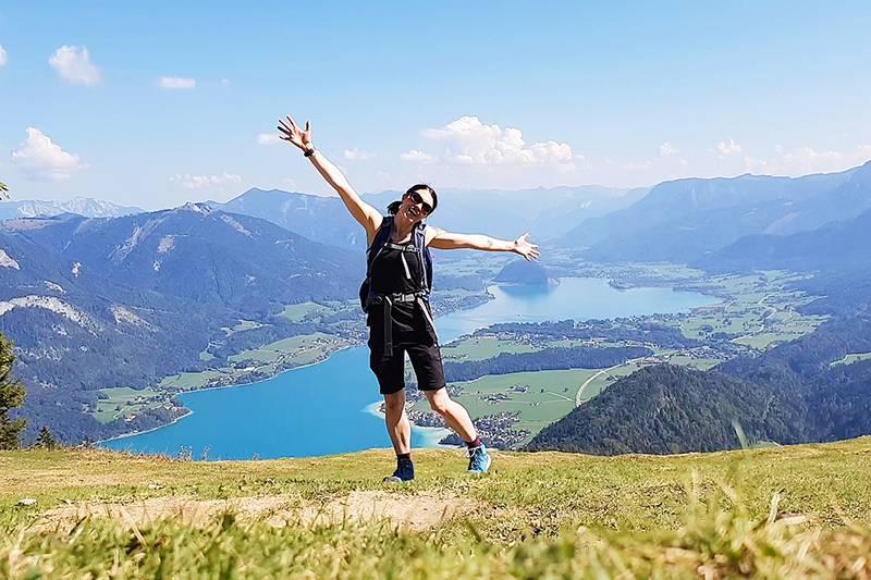 Woman standing on Zwölferhorn in Austria, overlooking Lake Wolfgang