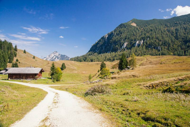 A hut in the mountains, surrounded by blue sky and green hills in Postalm, Austria
