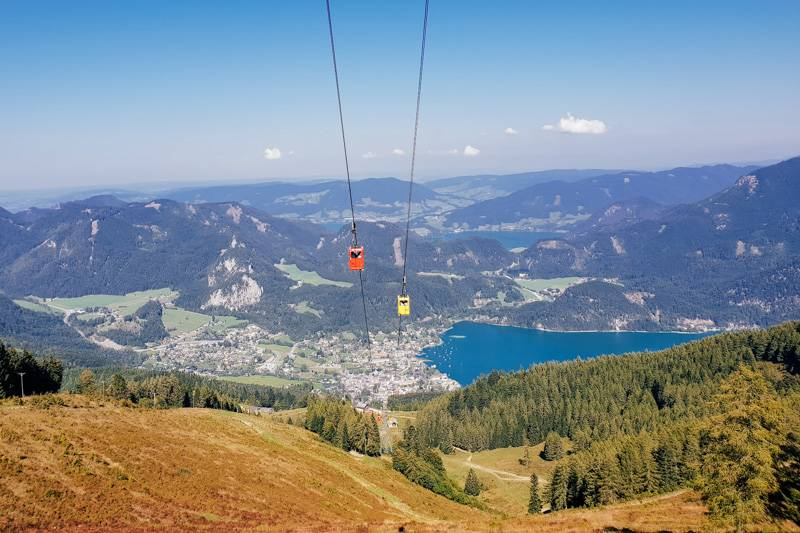 Cable cars travelling up and down Zwölferhorn mountain, with views of St. Gilgen below