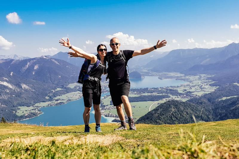 Couple standing on Zwölferhorn mountain, with views of Lake Wolfgang