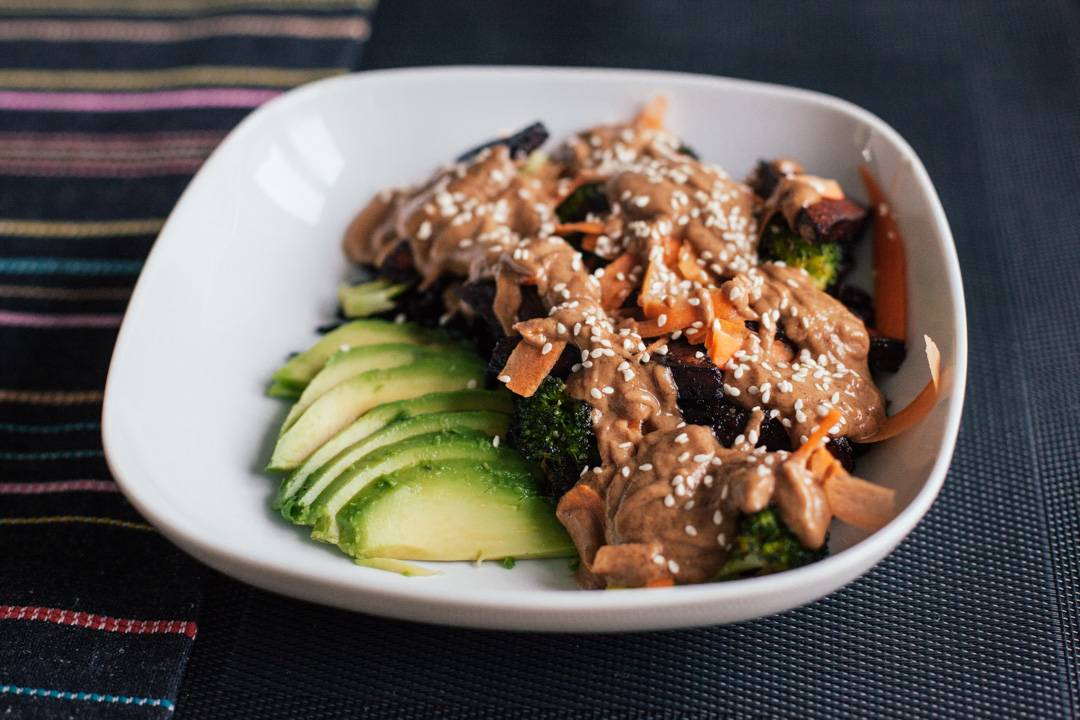 Vegan meal of avocado buddha bowl, with broccoli, black rice and peanut sauce
