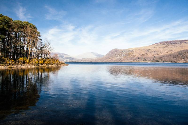 View across Derwent Water, with blue sky and fells in the background