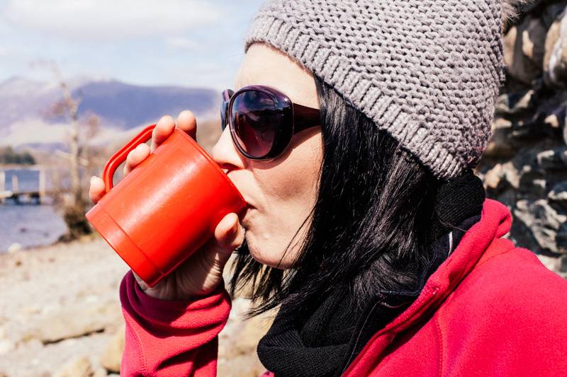 Woman dressed in a hat and outdoor clothing drinking a cup of tea