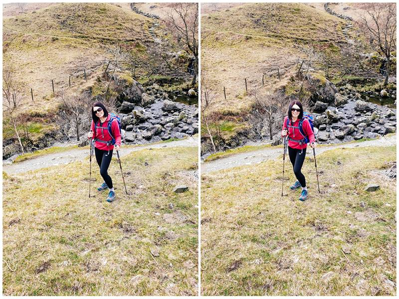 Smiling woman stood on a hillside, dressed in hiking clothes while holding hiking poles, in the Lake District