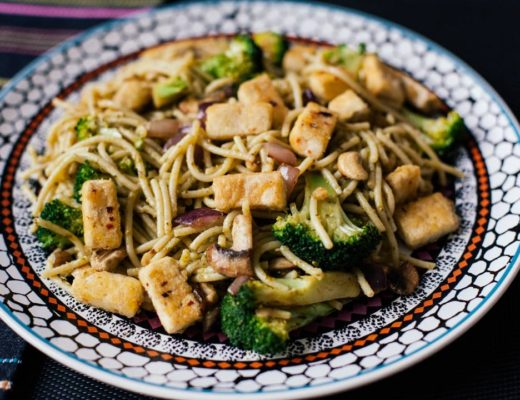 Vegan meal of tofu, broccoli, spaghetti and cashew nuts with pesto